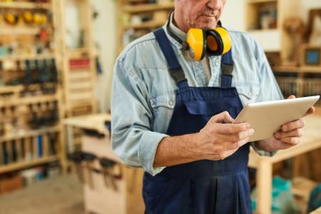 Photo pour Senior Carpenter using Tablet - image libre de droit