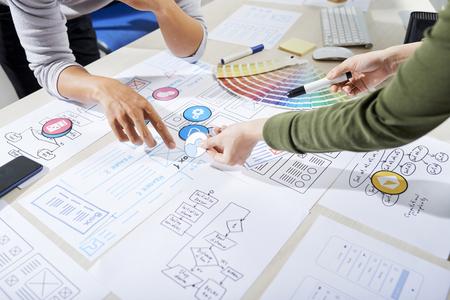 Foto de UX designers choosing icons for mobile application and discussing wireframe - Imagen libre de derechos
