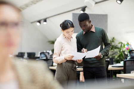 Photo pour Portrait of two business interns discussing documents standing in modern office, copy space - image libre de droit