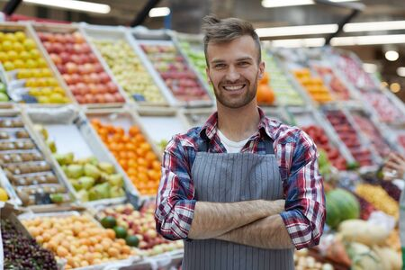 Foto de Waist up portrait of handsome young man working in supermarket and smiling at camera while posing by fruit stand, copy space - Imagen libre de derechos