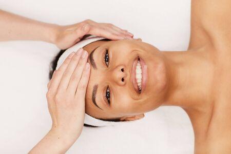 Photo pour Top view portrait of beautiful mixed-race woman enjoying face massage in luxury spa, copy space - image libre de droit