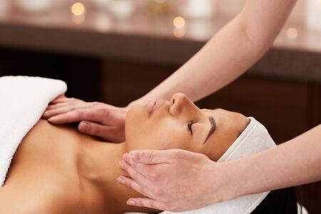 Foto de Side view of beautiful mixed-race woman enjoying face massage in luxury spa, copy space - Imagen libre de derechos