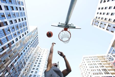 Photo pour Low angle view at African basketball player shooting slam dunk against sky in urban background, copy space - image libre de droit
