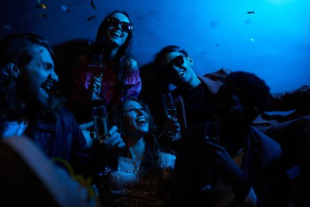 Photo pour Group of positive young friends laughing together and drinking champagne in dark room with blue light, girl excited about falling confetti - image libre de droit