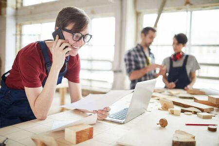 Photo pour Portrait of modern carpenters working at woodworking factory, focus on smiling young man speaking by phone and using laptop in foreground, copy space - image libre de droit