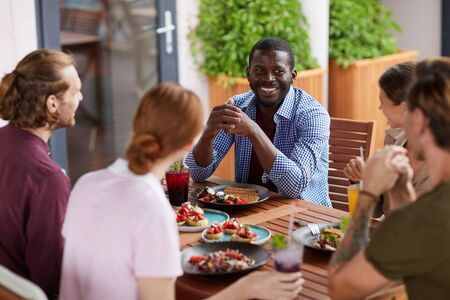 Photo for Multi-ethnic group of friends enjoying dinner together sitting at table and chatting cheerfully, focus on smiling African-American man, copy space - Royalty Free Image