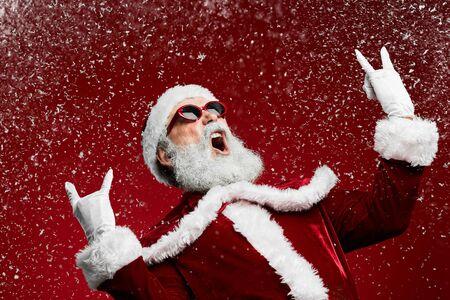 Photo pour Waist up portrait of cool rock Santa roaring over red background with snow falling, copy space - image libre de droit