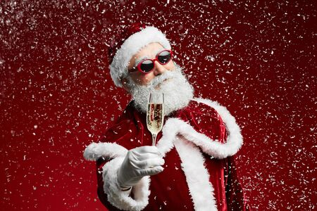 Photo pour Waist up portrait of cool Santa holding champagne glass while standing over red background with snow falling, copy space - image libre de droit