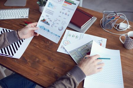 Foto de Closeup of unrecognizable modern businessman holding statistics report with colored data while working at wooden desk in office, copy space - Imagen libre de derechos