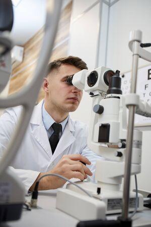 Photo pour Portrait of male optometrist using refractometer machine while testing vision of unrecognizable patient - image libre de droit