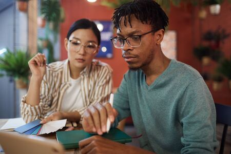Photo pour Portrait of contemporary African-American man using laptop while studying at table in cafe, copy space - image libre de droit