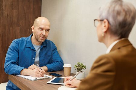 Photo pour Portrait of mature bald man writing on clipboard while discussing contract with business manager during meeting at cafe table, copy space - image libre de droit