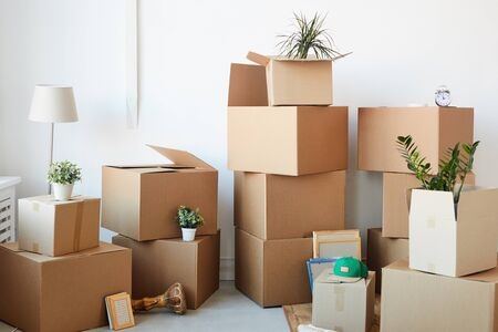 Photo pour Background image of cardboard boxes stacked in empty room with plants and personal belongings inside, moving or relocation concept, copy space - image libre de droit