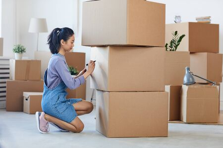 Photo pour Side view full length portrait of young Asian woman writing on cardboard boxes labeling them for moving out, copy space - image libre de droit