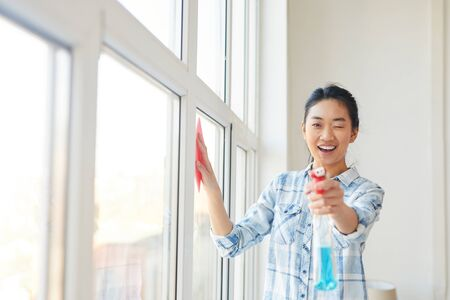 Photo pour Waist up portrait of young Asian woman pointing spray gun at camera while washing windows and enjoying Spring cleaning, copy space - image libre de droit