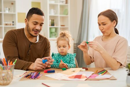 Photo pour Loving parents spending with their little daughter sitting together at table making models using play dough - image libre de droit