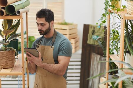 Photo pour Waist up portrait of bearded man wearing apron using digital tablet while counting stock in flower store, copy space - image libre de droit
