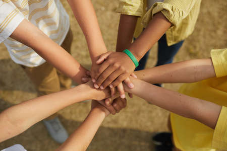 Photo pour Top view close up at multi-ethnic group of children stacking hands while standing in circle outdoors, concept of friendship and unity - image libre de droit