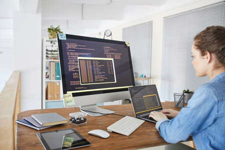 Photo pour Portrait of female IT developer typing on keyboard with black and orange programming code on computer screen and laptop in contemporary office interior, copy space - image libre de droit