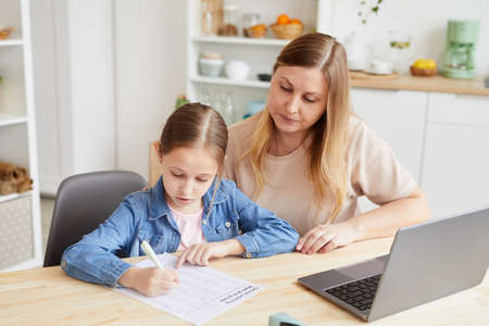 Photo pour Portrait of caring adult woman helping girl doing homework or studying at home while sitting at desk in cozy interior, copy space - image libre de droit