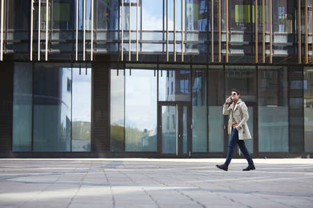 Photo pour Wide angle portrait of elegant businessman wearing trenchcoat walking across shot while speaking by smartphone, glass urban building in background - image libre de droit