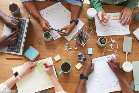 Photo pour Top view close up of multi-ethnic group of people working together at cluttered wooden table with coffee cups, mugs and stationary items, teamworking or studying concept, copy space - image libre de droit