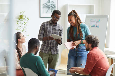 Photo pour Multi-ethnic group of people sitting in circle while discussing business project in office, focus on smiling African-American woman talking to colleague standing up , copy space - image libre de droit
