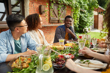 Photo pour Portrait of multi-ethnic group of friends enjoying dinner together outdoors while sitting at table on open terrace, focus on smiling African-American man sharing stories, copy space - image libre de droit