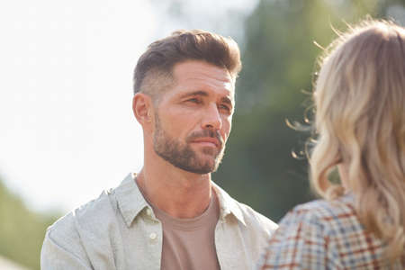 Photo pour Head and shoulders portrait of handsome adult man looking at girlfriend while enjoying romantic date outdoors in sunlight, copy space - image libre de droit