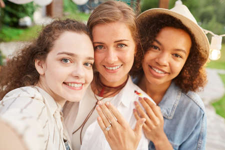 Photo pour POV portrait of beautiful young woman showing engagement ring taking selfie with friends during outdoor party - image libre de droit