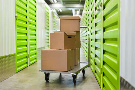 Photo pour Background image of cart with cardboard boxes in empty hall of self storage facility, copy space - image libre de droit
