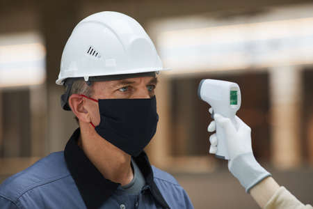Photo pour Portrait of mature worker wearing mask and waiting to measure temperature with contactless thermometer at construction site, corona virus safety - image libre de droit