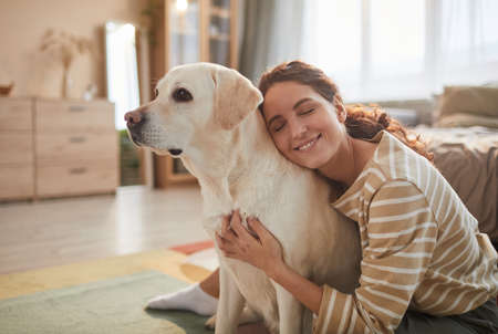 Photo pour Warm toned portrait of smiling young woman embracing dog while sitting on floor and enjoying time with loving pet, copy space - image libre de droit