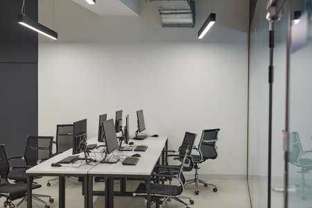 Photo pour Background image of empty office with multiple computer desks and chairs, IT lab concept, copy space - image libre de droit