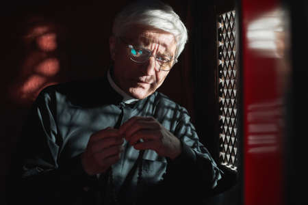 Photo pour Senior priest sitting with rosary beads sitting in confessional and listening to confession - image libre de droit