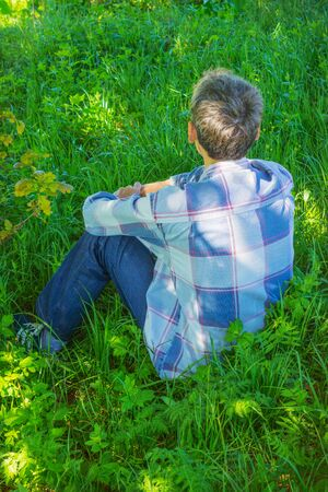 Young man is resting in the shade and looking into the distance