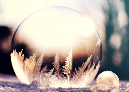 Photo pour Purple frozen soap bubble ball on snow in sunset, crystal formation, winter background with copy space - image libre de droit