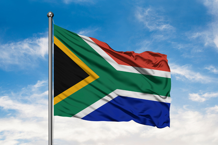 Flag of South Africa waving in the wind against white cloudy blue sky. South African flag.