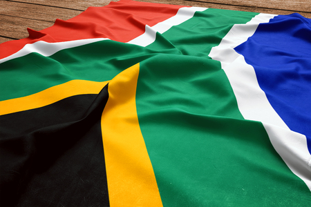 Photo pour Flag of South Africa on a wooden desk background. Silk South African flag top view. - image libre de droit