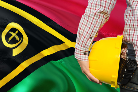 Engineer is holding yellow safety helmet with waving Vanuatu flag background. Construction and building concept.