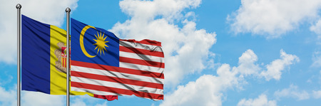 Andorra and Malaysia flag waving in the wind against white cloudy blue sky together. Diplomacy concept, international relations.