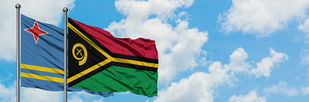 Aruba and Vanuatu flag waving in the wind against white cloudy blue sky together. Diplomacy concept, international relations.