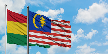 Bolivia and Malaysia flag waving in the wind against white cloudy blue sky together. Diplomacy concept, international relations.