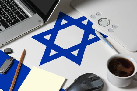 Photo for Israel national flag on top view work space of creative designer with laptop, computer keyboard, usb drive, graphic tablet, coffee cup, mouse on wooden table. - Royalty Free Image