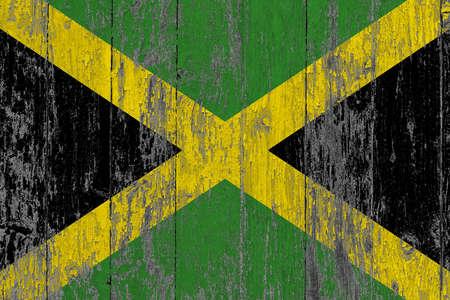 Foto de Jamaica flag on grunge scratched wooden surface. National vintage background. Old wooden table scratched flag surface. - Imagen libre de derechos