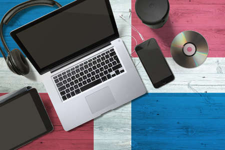 Dominican Republic flag on national background wooden table. Portable devices concept. Cd, headphones, tablet, notebook. Digital media theme.