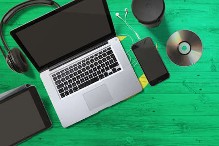 Mauritania flag on national background wooden table. Portable devices concept. Cd, headphones, tablet, notebook. Digital media theme.