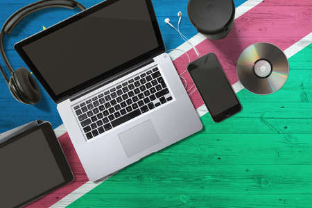 Namibia flag on national background wooden table. Portable devices concept. Cd, headphones, tablet, notebook. Digital media theme.