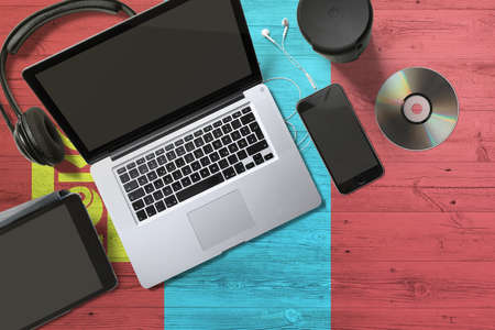 Mongolia flag on national background wooden table. Portable devices concept. Cd, headphones, tablet, notebook. Digital media theme.