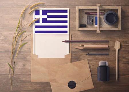 Photo pour Greece invitation, celebration letter concept. Flag with craft paper and envelope. Retro theme with divide, ink, wooden pen objects. - image libre de droit